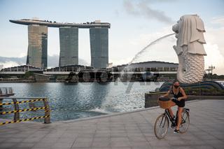 Singapur, Republik Singapur, Frau mit Mundschutz im Merlion Park und Marina Bay Sands Hotel im Hintergrund
