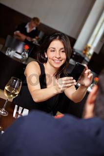 Frau fotografiert mit Handy im Restaurant