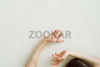 Woman's hands on the white wall, selective focus