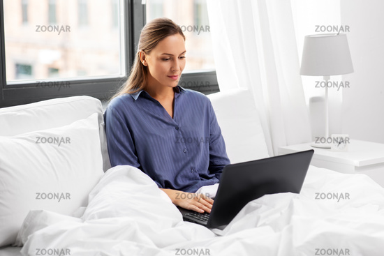 young woman with laptop in bed at home bedroom