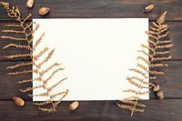 Blank paper on wooden table and autumn decoration