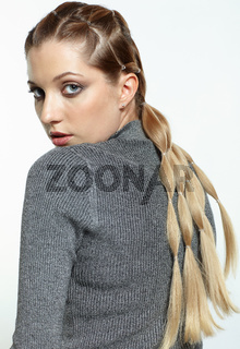 back view portrait of blonde female with creative braid hairdo.