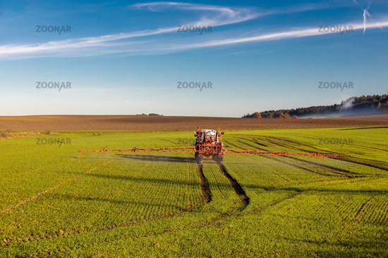 Farmer with tractor spraying herbicide