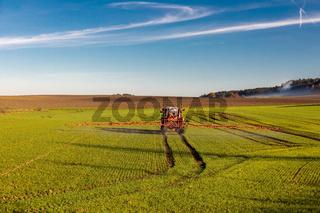 Landwirt mit Traktor sprueht Pflanzenschutzmittel