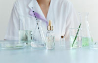 Woman examining green plant in laboratory
