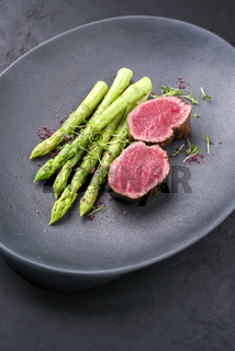 Barbecue dry aged wagyu beef fillet head medallion steak natural with green asparagus and herbs as closeup on a modern design plate with copy space
