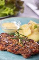 gegrilltes Schweinesteak mit Kartoffelsalat