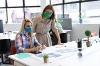 Two diverse businesswomen wearing face masks looking at blueprints and discussing