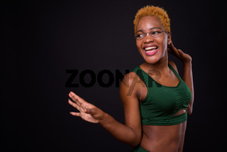 Young beautiful African woman against black background