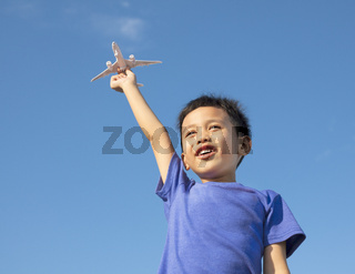 happy boy holding a airplane toy with blue sky