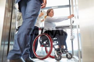 Frau als Rollstuhlfahrer drückt Taste im Fahrstuhl
