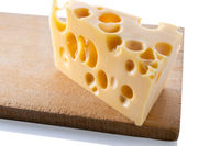 Swiss cheese on a wooden board, isolated close up