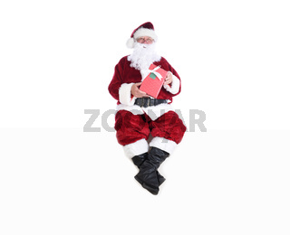 Senior man in traditional Santa Claus Suit sitting on a white wall and holding a wrapped present.