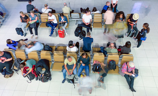 Tourists awaiting flight in the terminal hall, blurred view of moving people