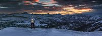 Hiker Man with Backpack standing on snow winter mountain with view to amazing sunset alpenglow panorama of mountain ranges and dramatic sky. View from Riedbergerhorn to Allgau Alps. Bavaria, Germany.