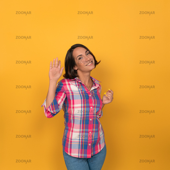 Welcoming woman waves smiling coquettishly at camera. Cute young brunette wearing jeans and checkered shirt showing hello. Isolated on yellow. Copy space
