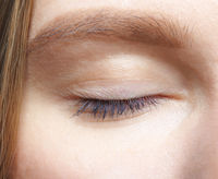 Closeup macro shot of closed human female eye.