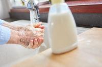 Senior beim Händewaschen mit Seife im Bad