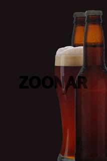 A glass of dark beer between two brown beer bottles against black background