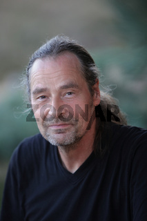 Charismatic middle-aged man with a ponytail