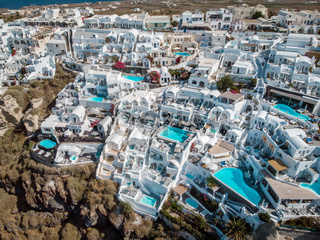 Drone view over Santorini, aerial view over the whitewashed village of Oia with luxury vacation resort with infinity pools in Santorini Greece