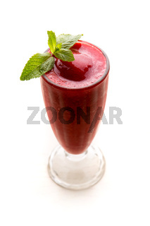 Red cocktail, smoothie, juice in a transparent glass with water droplets. Isolated on a white background. Cocktail decoration: mint, orange, lemon, ice cubes. Healthy eating.