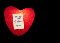 R Heart with a sticky note and the text P.S. I LOVE YOU isolated on black background