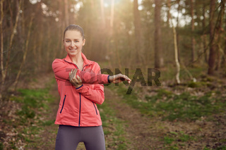 Happy fit woman stretching her arm outdoors