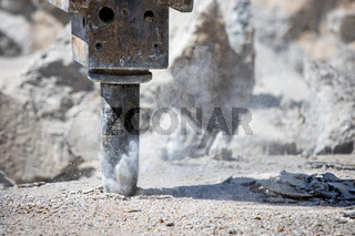 Jackhammer hammering concrete for hole and making dust