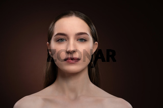 Strong look girl face portrait with natural make up and bare shoulders. Healthy pure skin model isolated on black background. Natural make up concept. Spa and beautiful concept