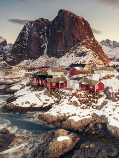 Iconic red stilt houses on the coast in the village  Hamnøy on the Lofoten islands in Norway on clear winter morning with snow-clad steep mountain