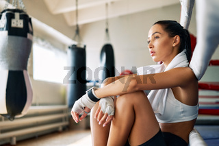 Young beautiful woman relax after fight or workout exercising in boxing ring