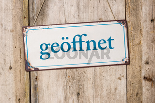 Old metal sign in front of a rustic wooden wall - Open - geoeffnet German