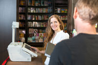 Cashier in bookstore serving a customer or client