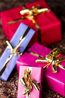 Vier Geschenkpäckchen mit goldener Schleife