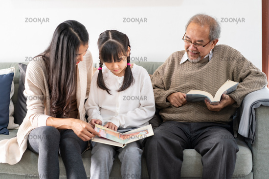 Daughter reading story with mom and grandfather
