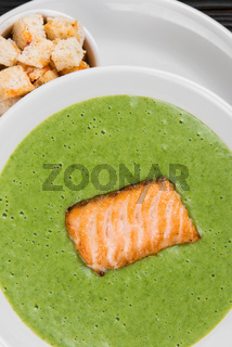 Delicious green broccoli cream-soup with salmon