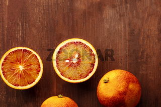 A closeup photo of organic blood oranges, shot from the top on a dark rustic background