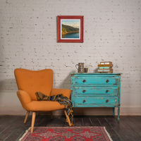 Vintage turquoise cabinet with orange stylish armchair in room interior
