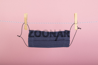 homemade mouth covering,face mask hanging on a clothesline, fixed with a clothespin, rose background