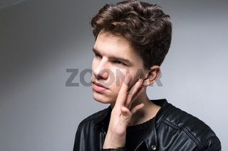 Wide angle. Studio shot. Young caucasian guy model in black clothes posing in the studio. Teenager in Leather Jacket Standing at White Background. young fashion model wearing black coat in studio