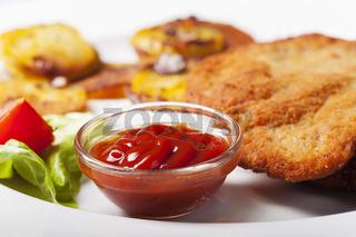 Ketchup mit einem Wiener Schnitzel und Bratkartoffeln