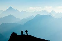 Two Men reaching summit after climbing and hiking enjoying freedom and looking towards mountains silhouettes panorama during sunrise.