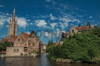 Steeple and old buildings on canal of Bruges