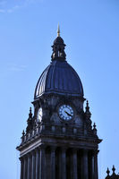 close up of the dome and clock tower of leeds city hall in west yorkshire against a blue sky