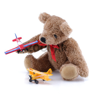 Small cute teddy playing with toy planes