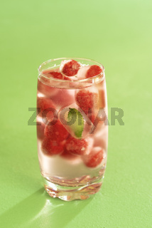 Glass of water and frozen fruits. Iced raspberries.