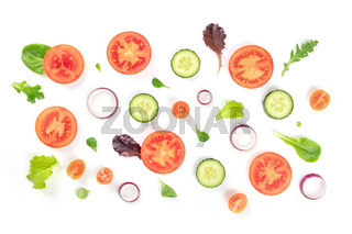 Fresh vegetable salad ingredients, shot from the top on a white background. A flat lay composition with tomato, cucumber, onion, and mezclun leaves