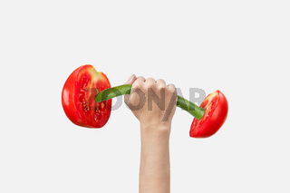 Woman hand holds sport barbell made from natural cut tomatoes.