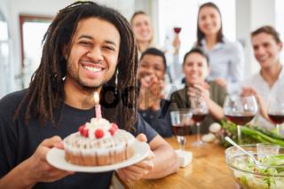 Mann hält Kuchen mit Kerze am Geburtstag bei seiner Geburtstagsfeier